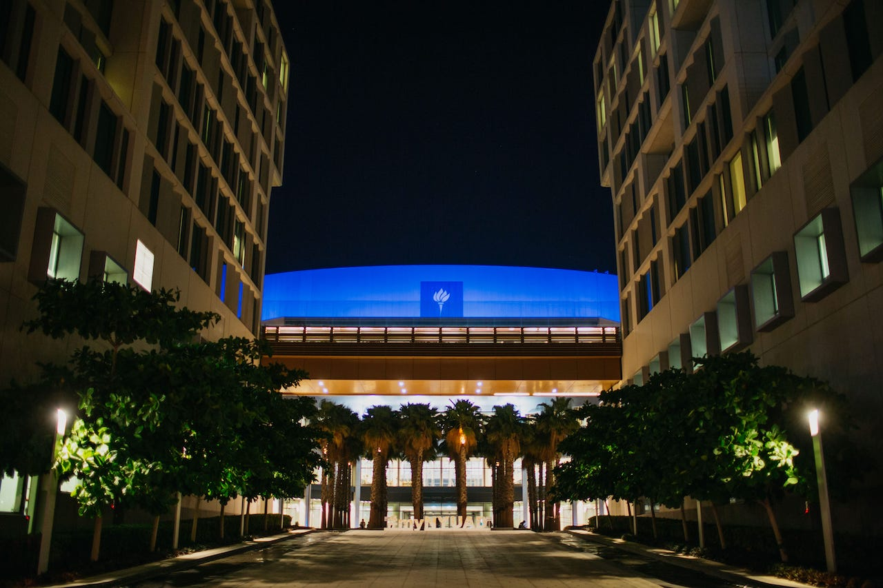 A nighttime shot of the NYU Abu Dhabi campus lit up, promoting community engagement through Autism Awareness Month.