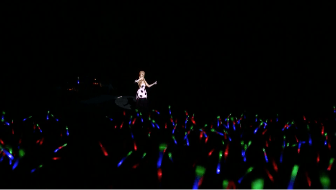 Host of ultraviolet live, Alaska waves a glow stick along with the audience.