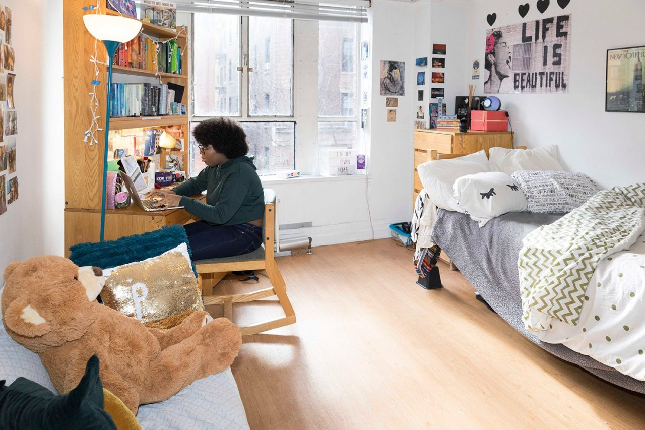 A student sits in her residence hall room.