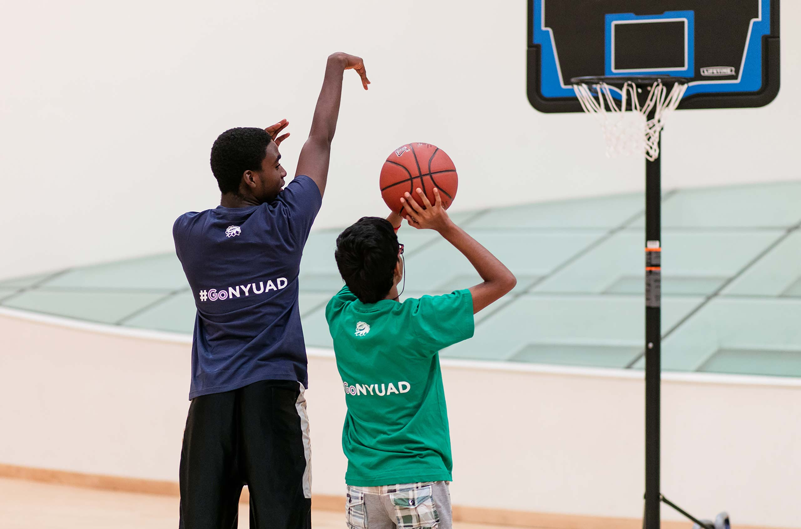NYU Abu Dhabi student demonstrating to a child how to properly shoot a basketball