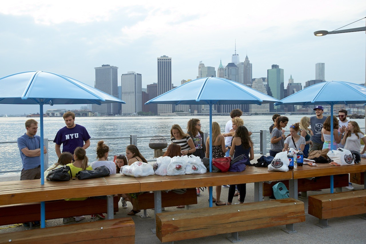 [Students barbecue while taking in the views of lower Manhattan from Brooklyn Bridge Park.]