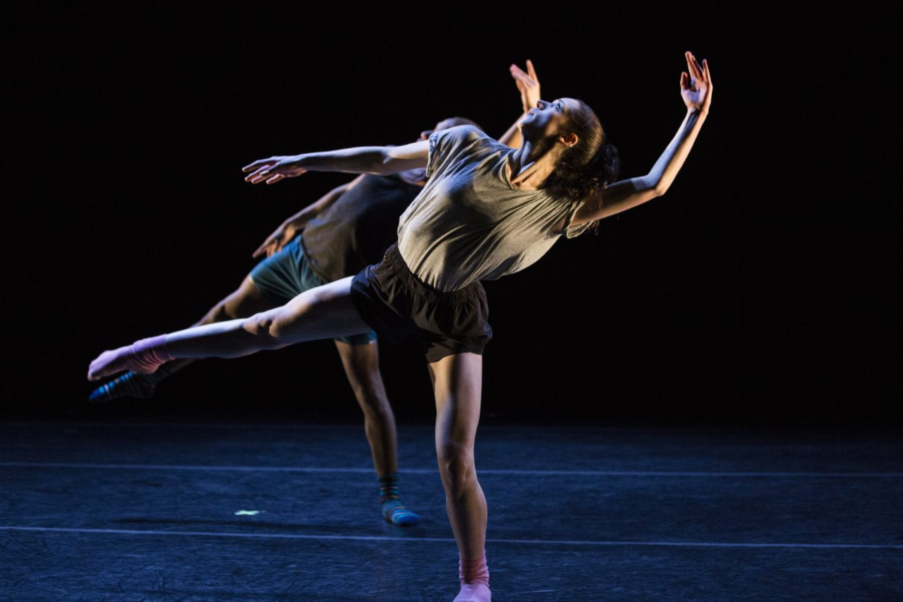 Two students performing modern dance onstage.