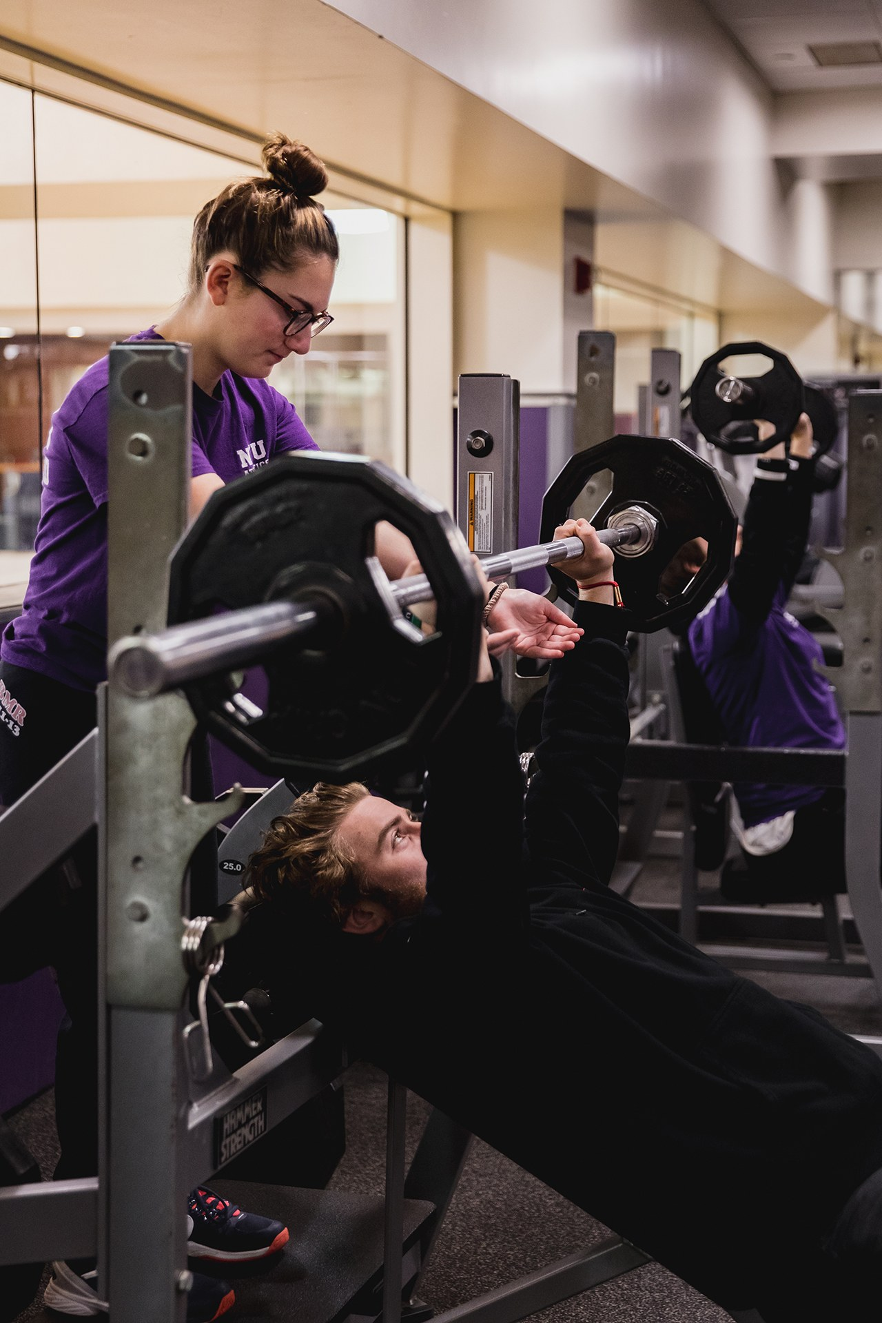 Student lifting large weight on bench while another student spots them.