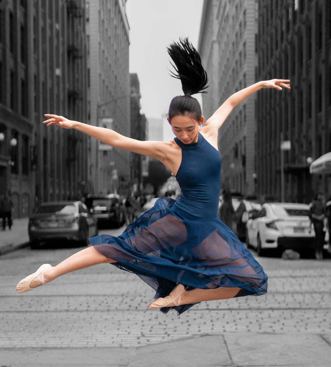 Dancer leaps in the air in the middle of a cobblestone street in Brooklyn.