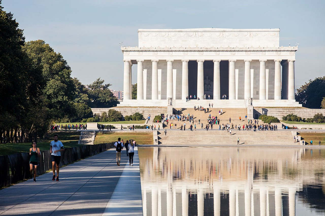 Pedestrians walk around the Lincoln Memorial Reflecting Pool and sit on the steps of the Lincoln Memorial.