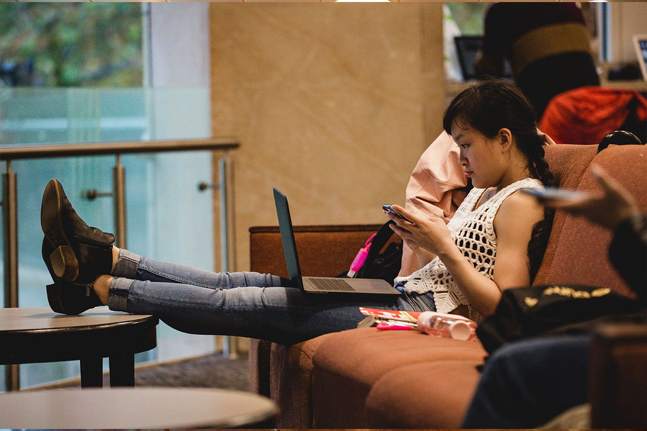 Student studying in a lounge chair.
