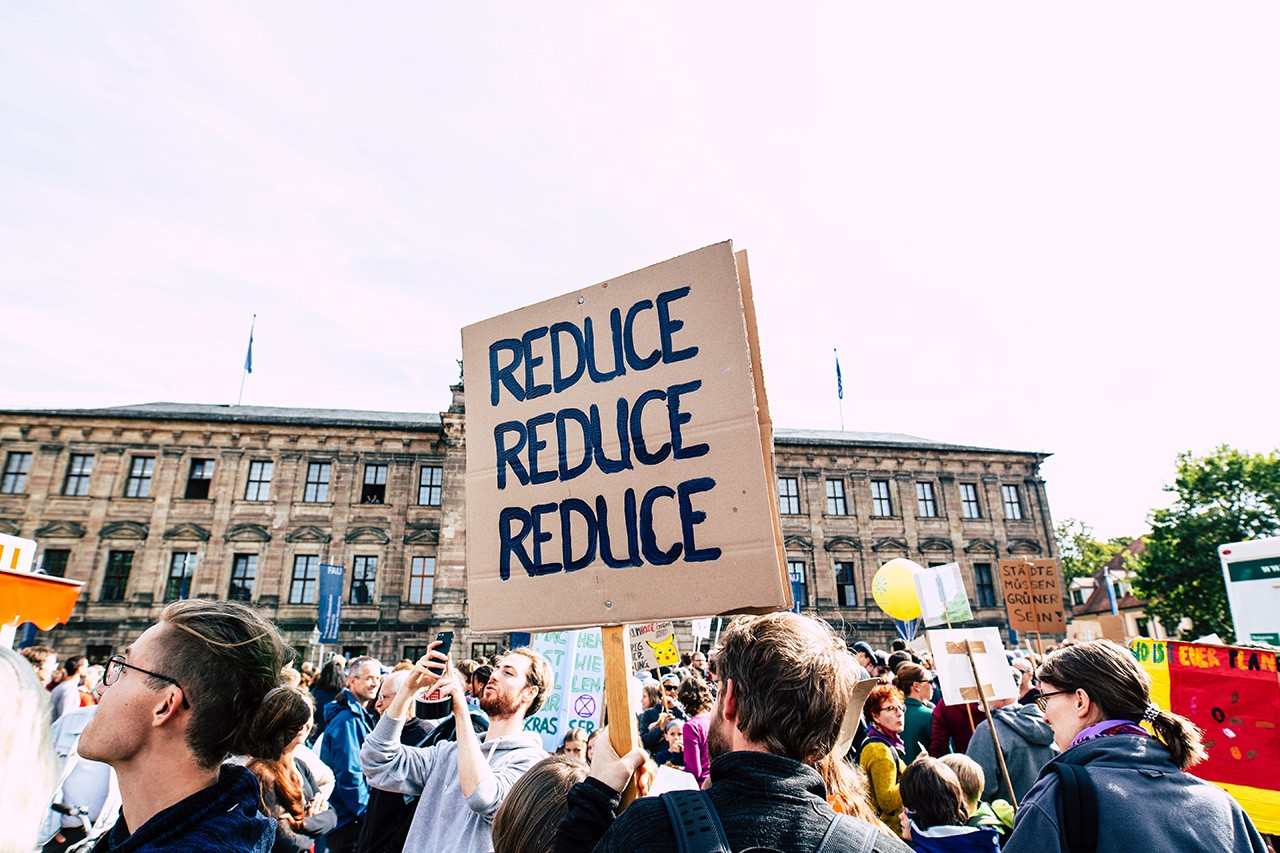 "Protestor holding a sign, reading ""Reduce, Reduce, Reduce,"" to promote waste reduction."
