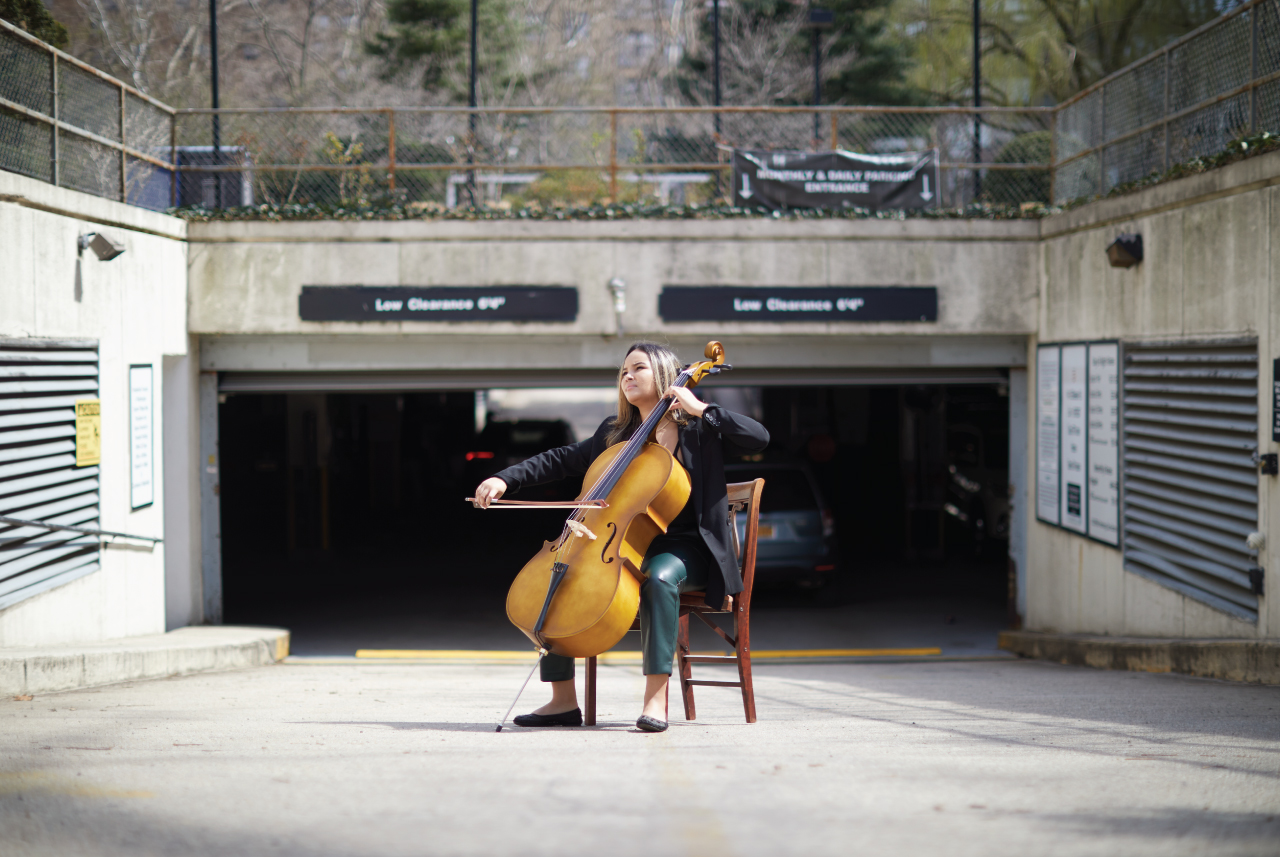 A girl playing a cello in front of a parking garage.
